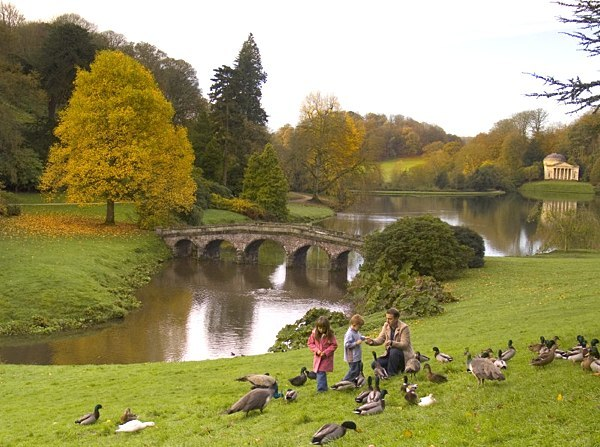 The Palladian Bridge at Stourhead, Wiltshire, with a family visiting the landscape garden to enjoy the autumn colours © National Trust Images/Ian Shaw