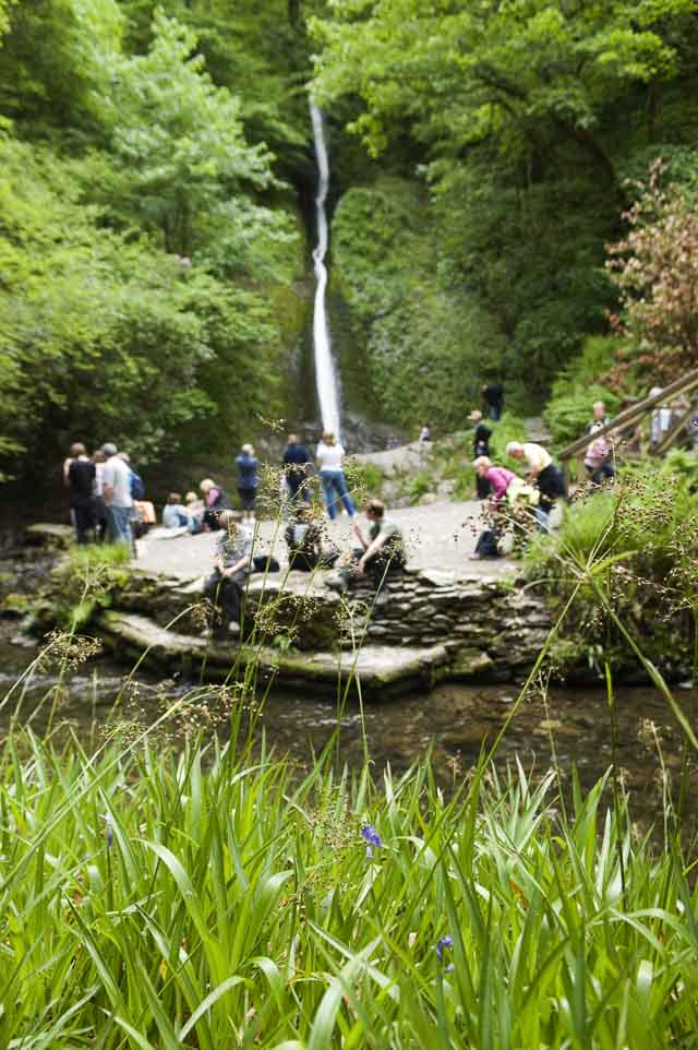 Visitors admiring the view of the Whitelady Waterfall at Lydford Gorge, Devon